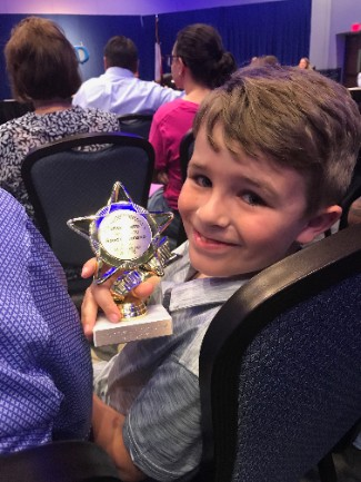 first-grade boy poses with his superintendent star award